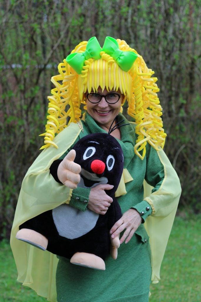 Kuva Agenda Toivosesta. Hymyilevä nainen jolla on vihreä mekko ja keltainen iso peruukki. Sylissä Myyrä-pehmolelu.