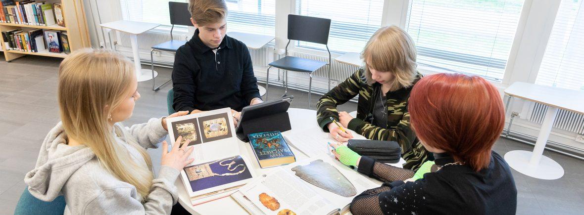 Nuoria tekemässä koulutehtäviä pyöreän pöydän ääressä.