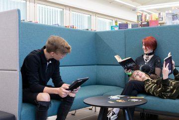 Nuoria sohvalla lukemassa kirjoja.